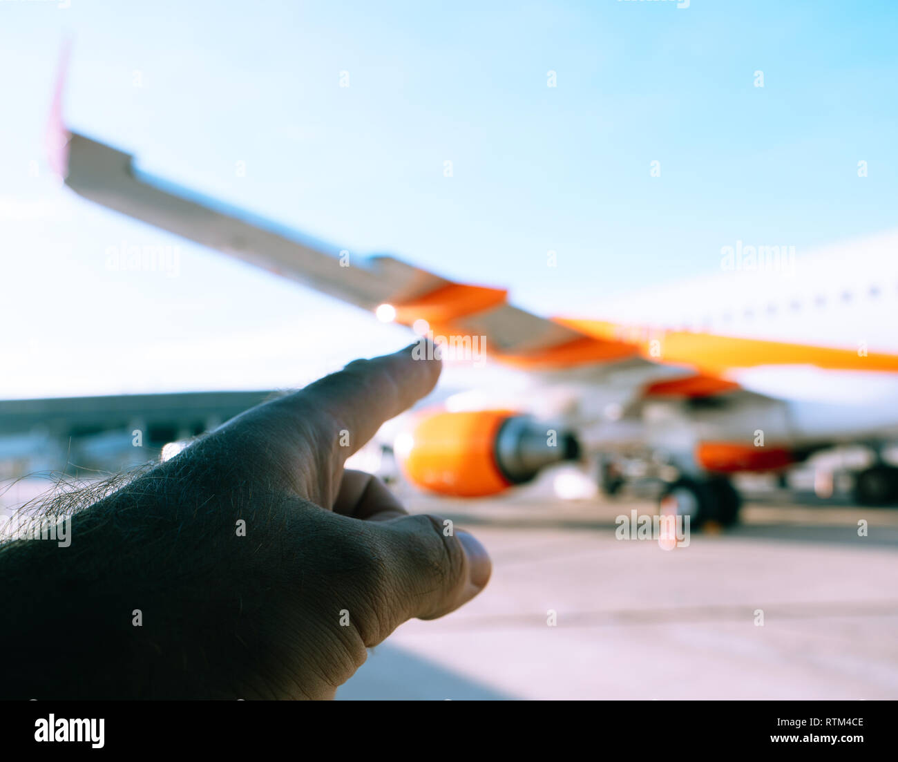 Finger pointing to the orange airplane on the tamrac of a modern airport - Stock Image