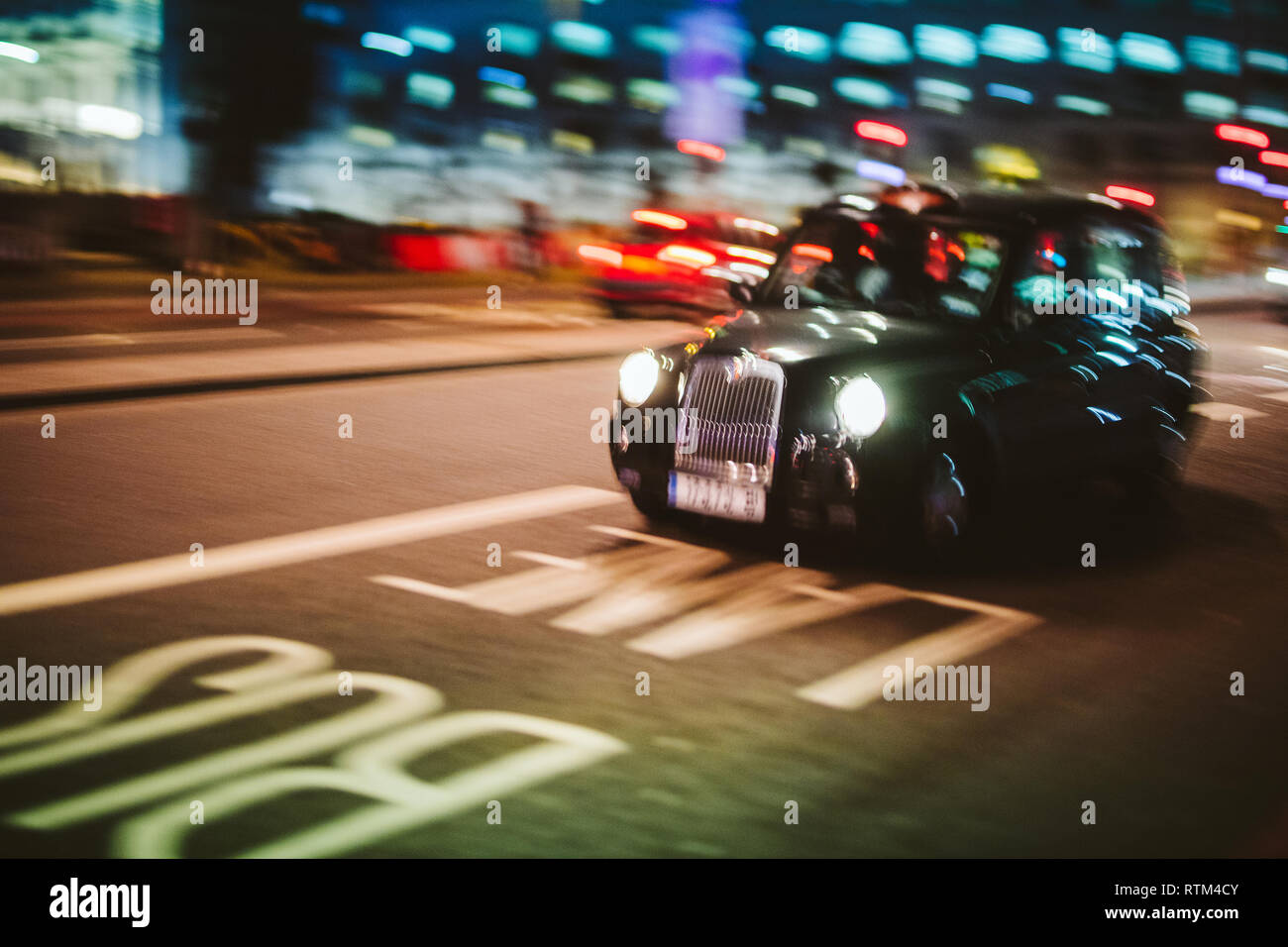 Abstract defocused in motion British Taxi hackney carriage cab driving fast to destination on the London street at night - transportation business theme with defocused motion on Bus lane and bokeh - Stock Image