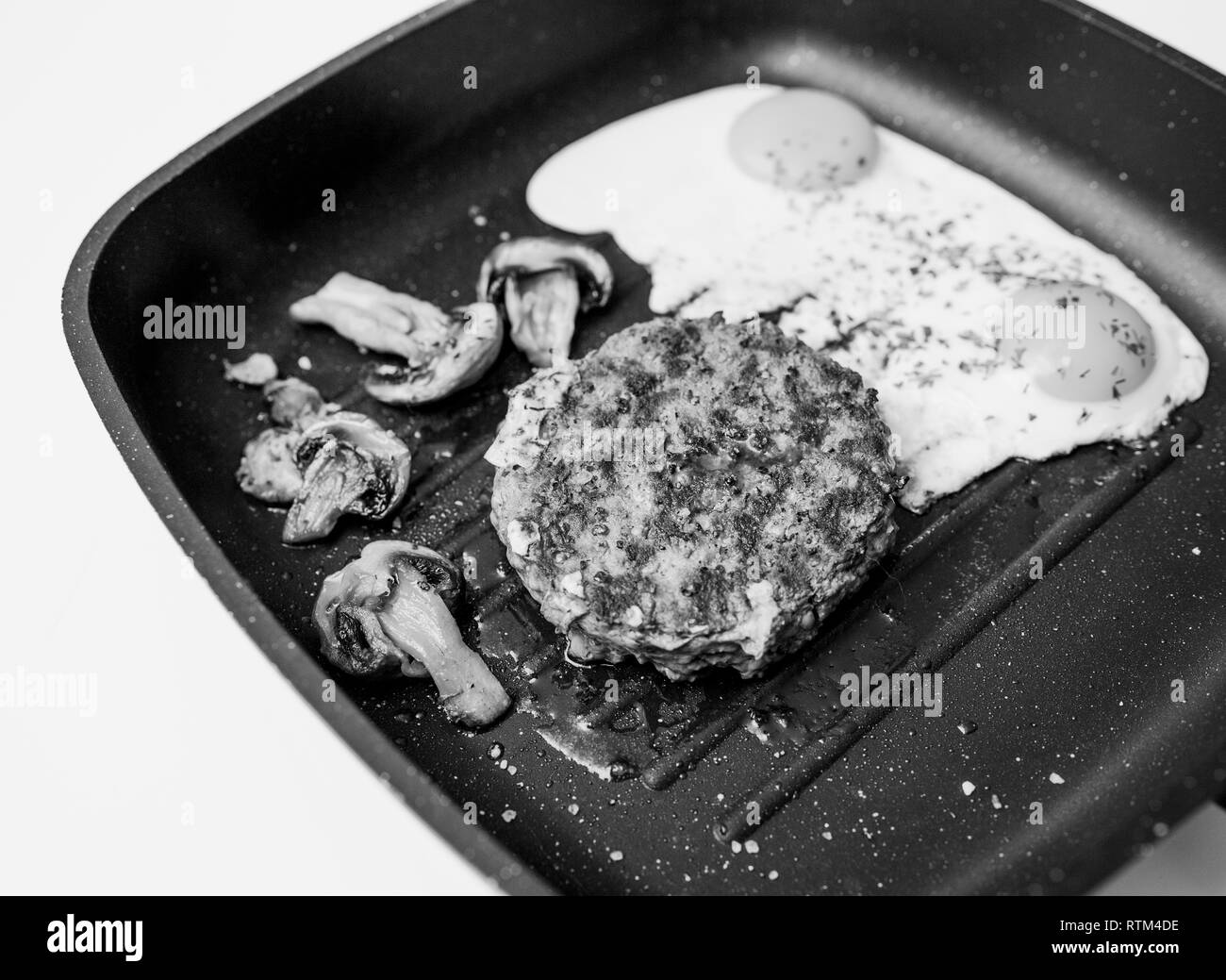 Above of delicious raw beef meat burger cooked in frying pan on teflon grill surface in kitchen with two fried eggs with organic fried champignons black and white image  - Stock Image