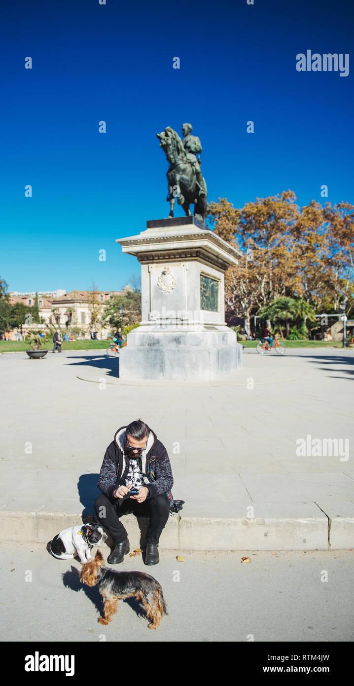 BARCELONA, SPAIN - NOV 12, 2017: Spanish man with two small dogs using smartphone near Estatua equestre del general Prim statue monument in Parc de la Ciutadella on a warm summer sunny day  - Stock Image