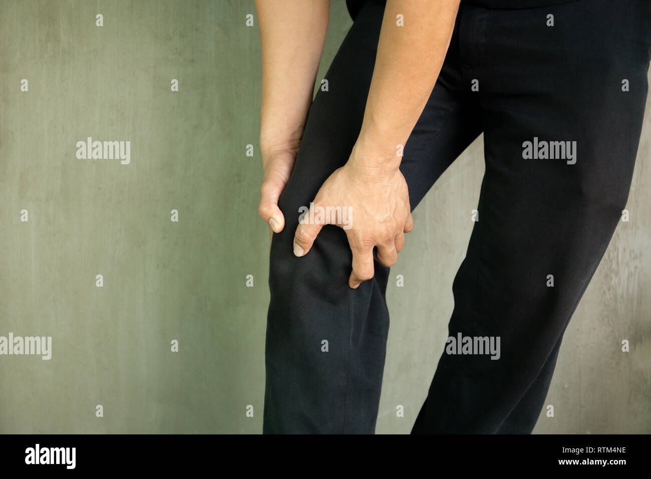 Man grab his knee experiencing pain isolated in grey background - Stock Image