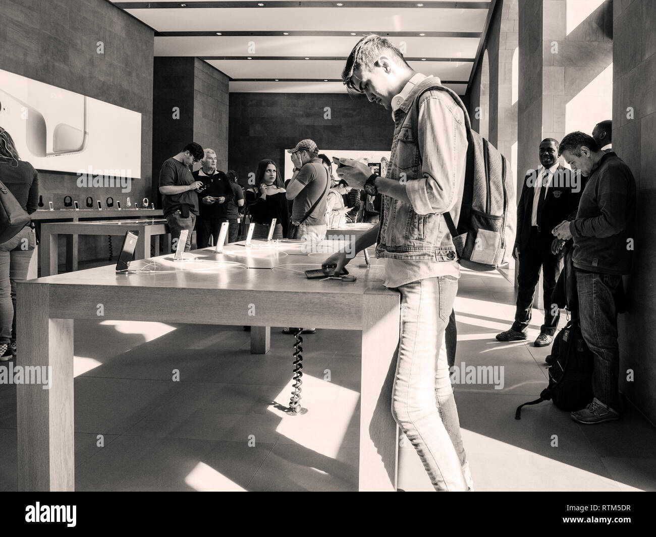 PARIS, FRANCE - SEP 22, 2017: New iPhone 8 and iPhone 8 Plus, as well the updated Apple Watch, Apple TV goes on sale today in Apple Store with customer male testing phone  Stock Photo