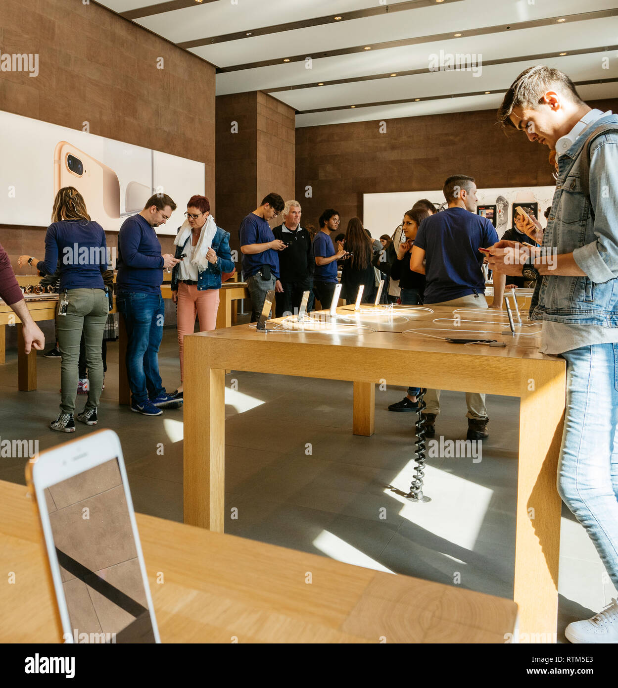 PARIS, FRANCE - SEP 22, 2017: New iPhone 8 and iPhone 8 Plus, as well the updated Apple Watch, Apple TV goes on sale today in Apple Store with customers looking at the phone  Stock Photo
