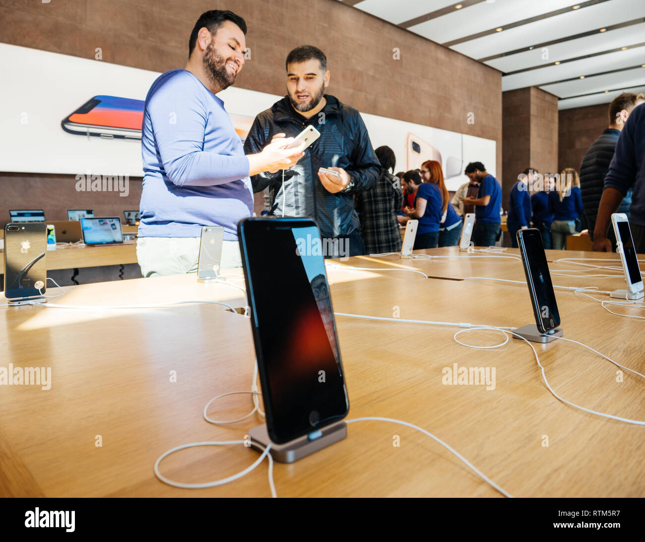 PARIS, FRANCE - SEP 22, 2017: New iPhone 8 and iPhone 8 Plus charging in docking station goes on sale today in Apple Store with middle East ethnicity customers holding admiring the phone Stock Photo