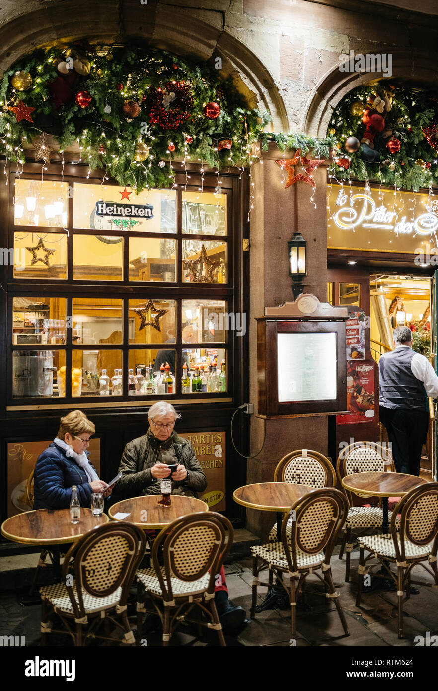 STRASBOURG, FRANCE - NOV 21, 2017: Le Pilier des Anges French restaurant on the iconic Rue Merciere with senior couple eating at the outdoor cafe paying the bill to the waiter - Stock Image