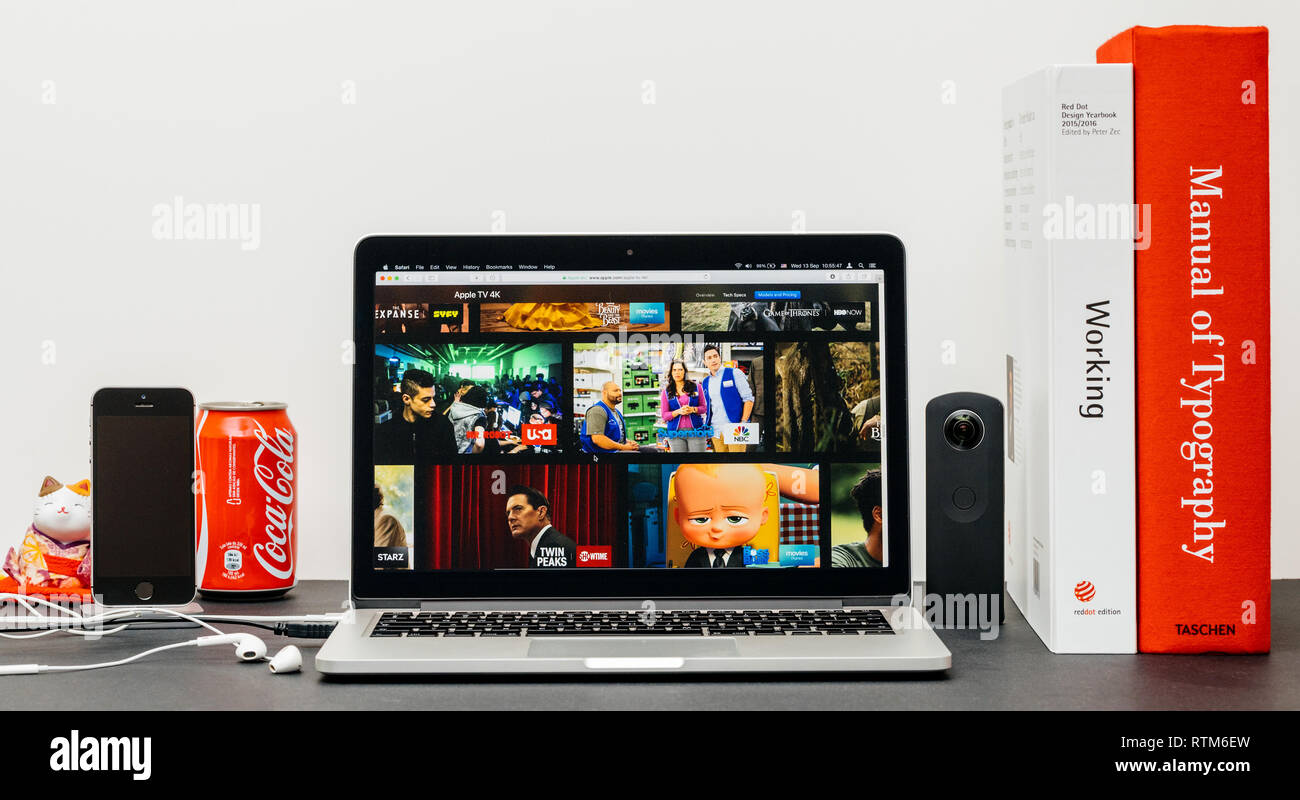 PARIS, FRANCE - SEP 13, 2017: Minimalist creative room table with Safari Browser open on MacPook Pro laptop showcasing Apple Computers website with latest Apple TV 4k with major broadcasters channels  Stock Photo