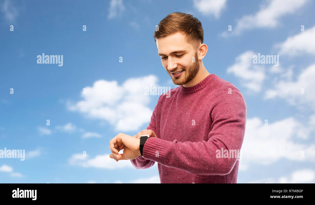 smiling young man checking time on wristwatch - Stock Image