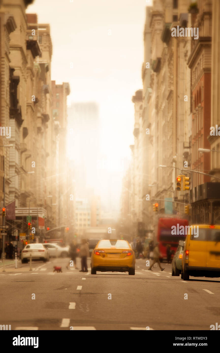 Sunlight shines on New York City urban street with anonymous blurred people, cars and yellow taxi cabs - Stock Image