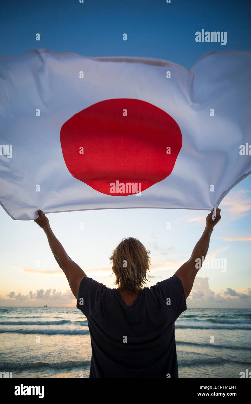 Scenic sunrise silhouette of man holding Japanese flag in front of soft morning sky above a beach with waves approaching on the horizon - Stock Image