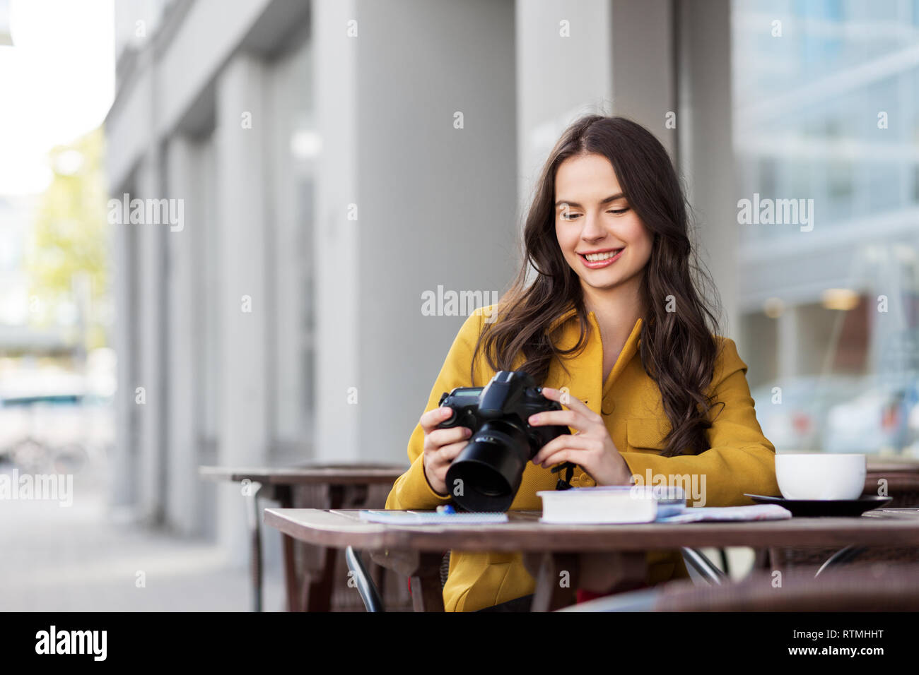 tourist or teenage girl with camera at city cafe - Stock Image