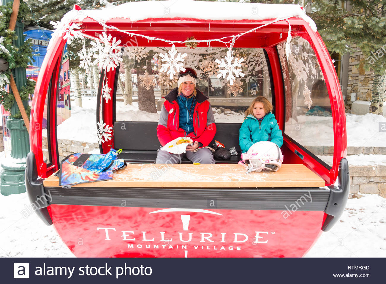 Female ski instructor eating lunch with student in prop gondola, Heritage Plaza, Mountain Village, San Miguel County, Colorado, USA - Stock Image