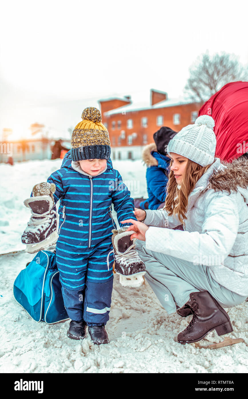 A little boy is 3-6 years old, in the winter in the city on a public skating rink. In a blue jumpsuit and a warm hat, holds skates in his hand. Mom - Stock Image