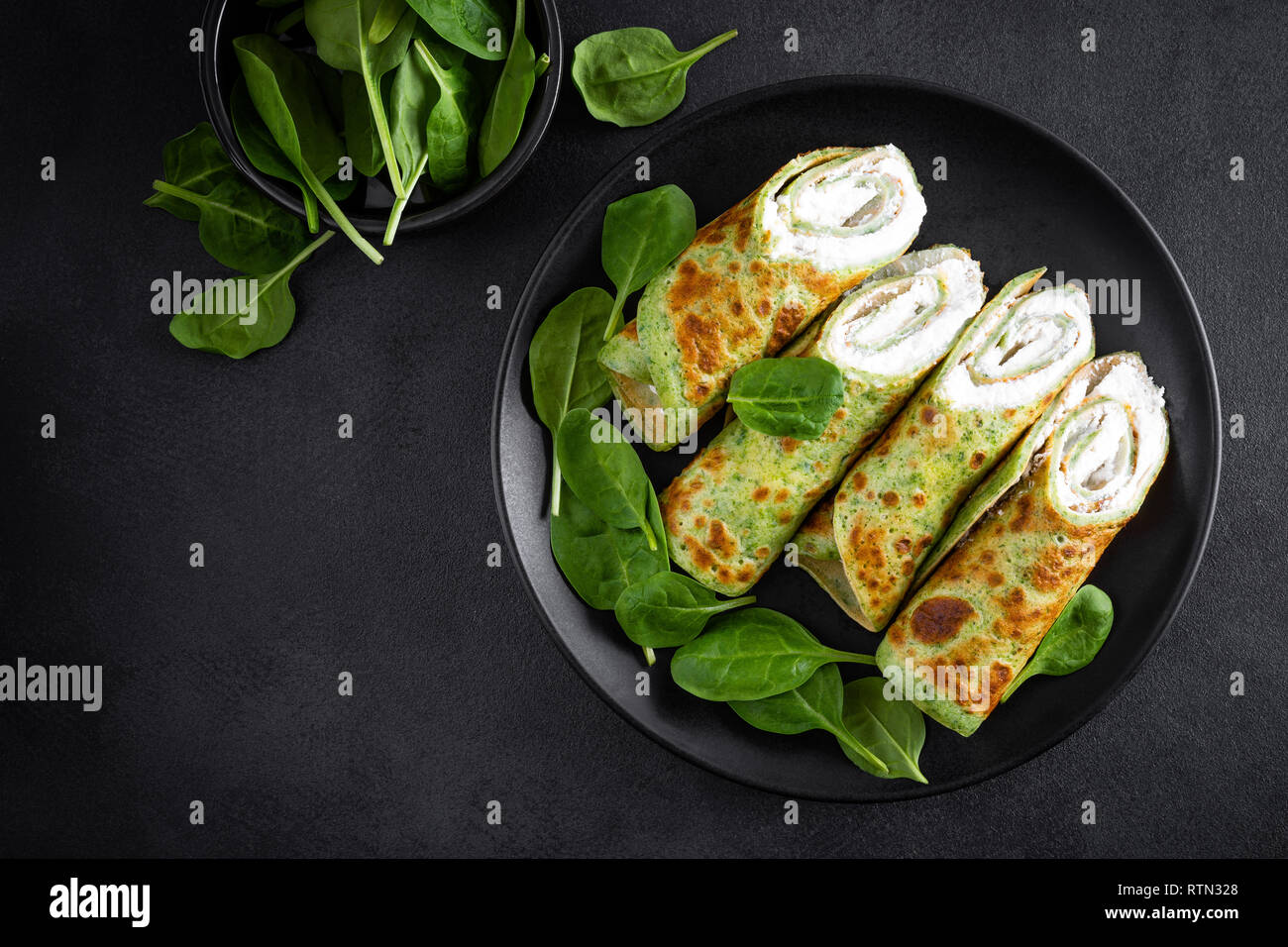 Savory crepes with spinach and feta cheese on black background, top view - Stock Image