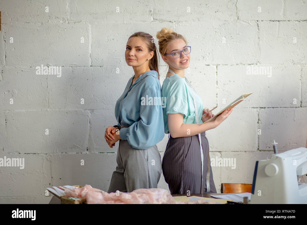 Portrait of two pretty young female seamstresses, fashionably dressed in pastel colours, standing back to back and looking at camera in bespoke clothi - Stock Image