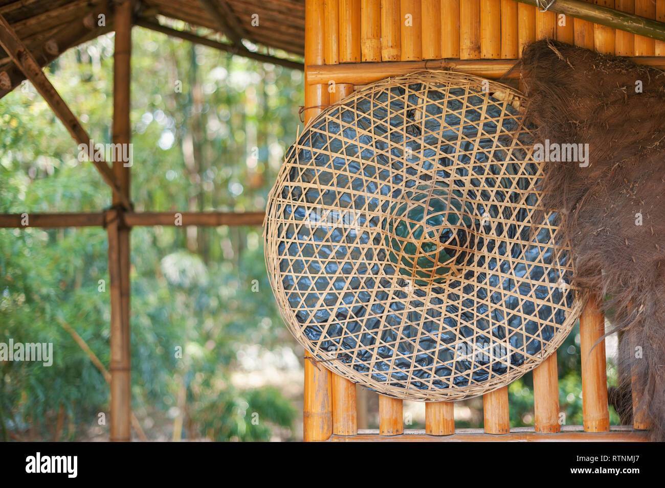 22aa38487 Chinese straw hat hanging on a bamboo wall in the countryside, China -  Stock Image