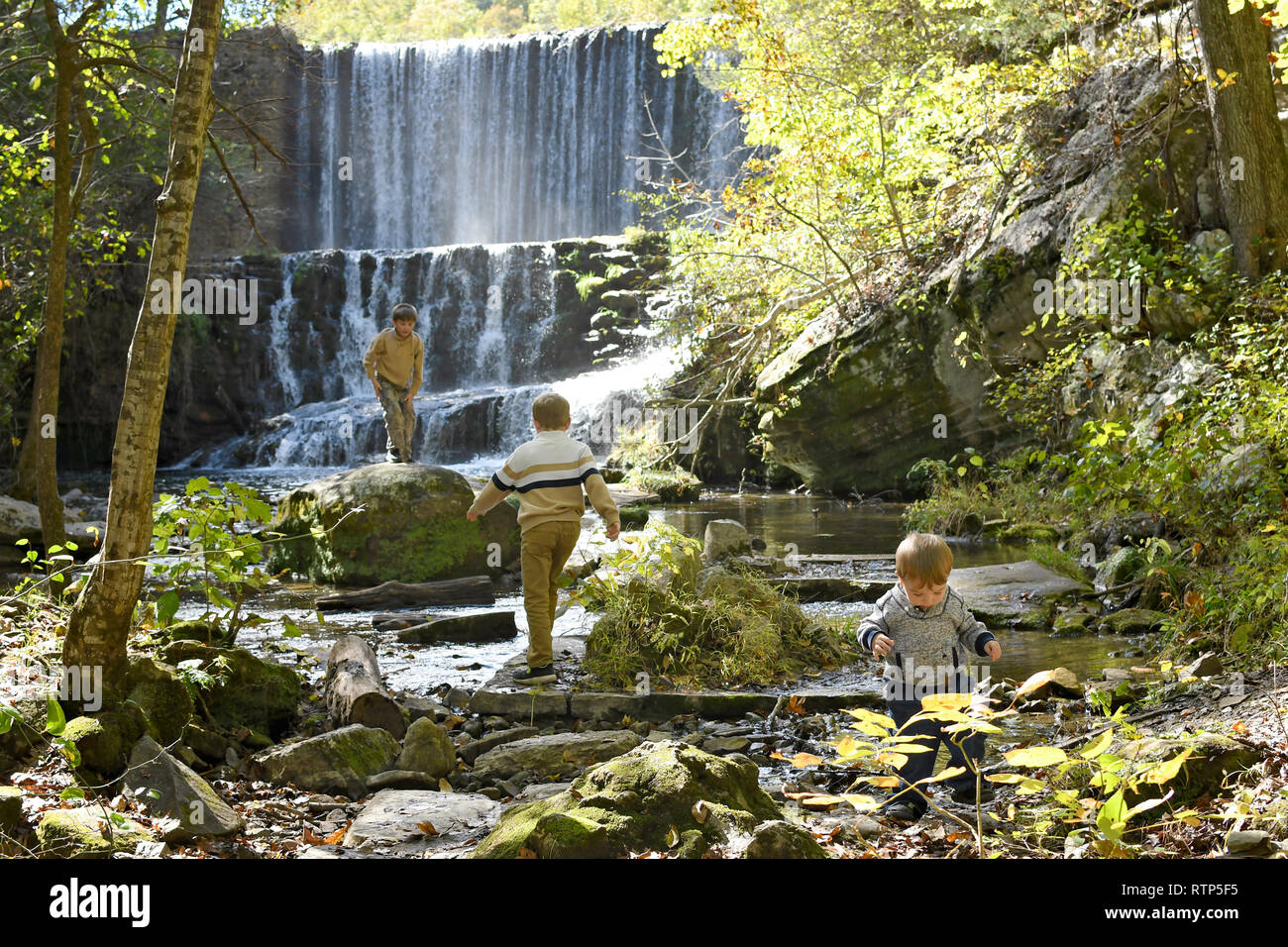 Three boys playing in a waterfall and nearby creek - Stock Image