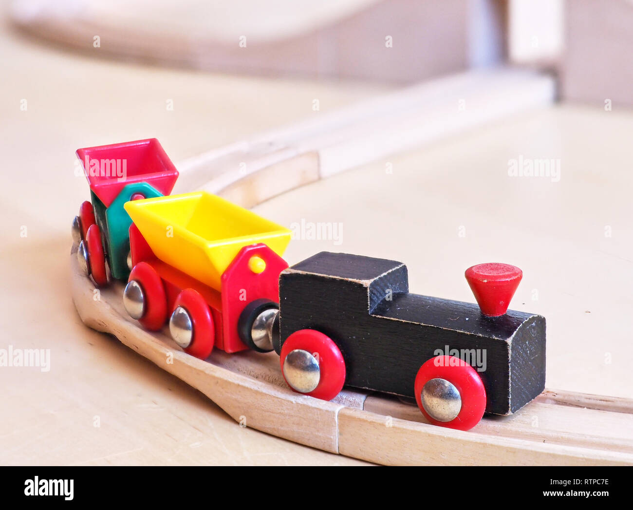 Wooden toy train running on miniature tracks  The black