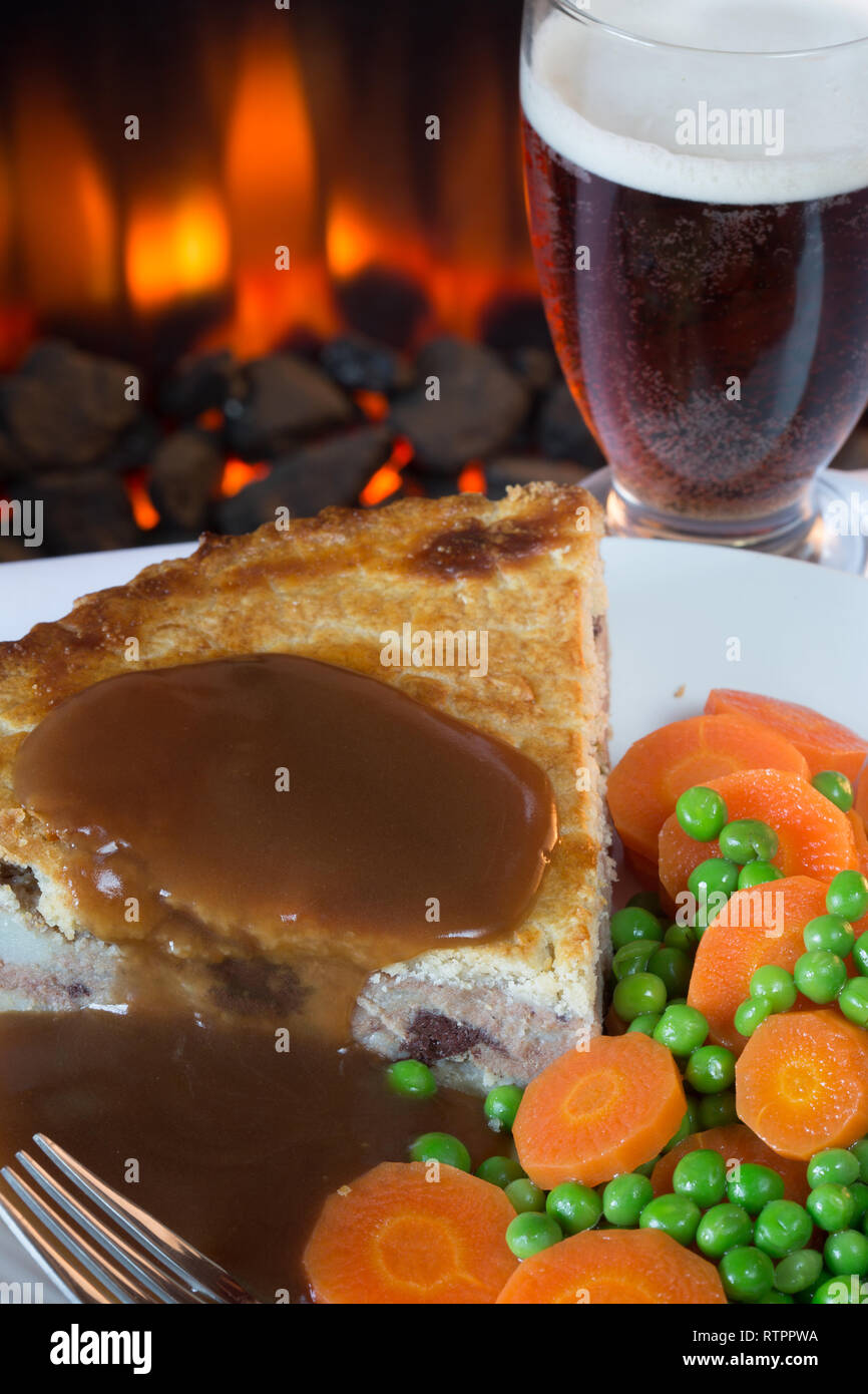 Meat and potato pie with garden peas and carrots served with gravy sauce - Stock Image