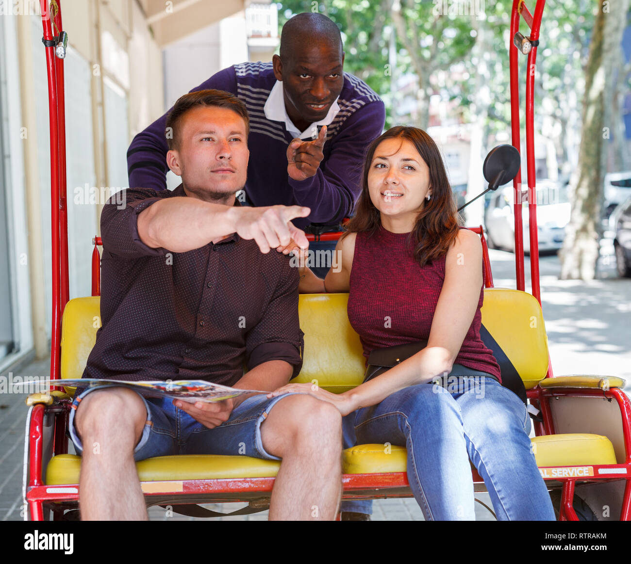 Young loving couple enjoying tour of city on trishaw with affable African American driver - Stock Image