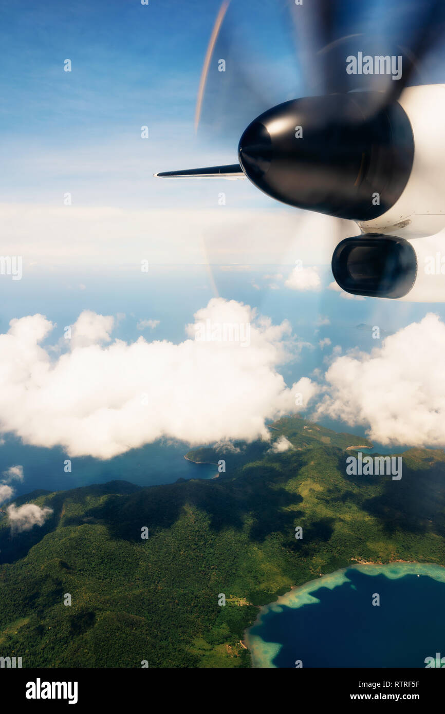 Propeller aircraft wing over tropical islands. Aerial view of airplane flying above shade clouds and sky - Stock Image