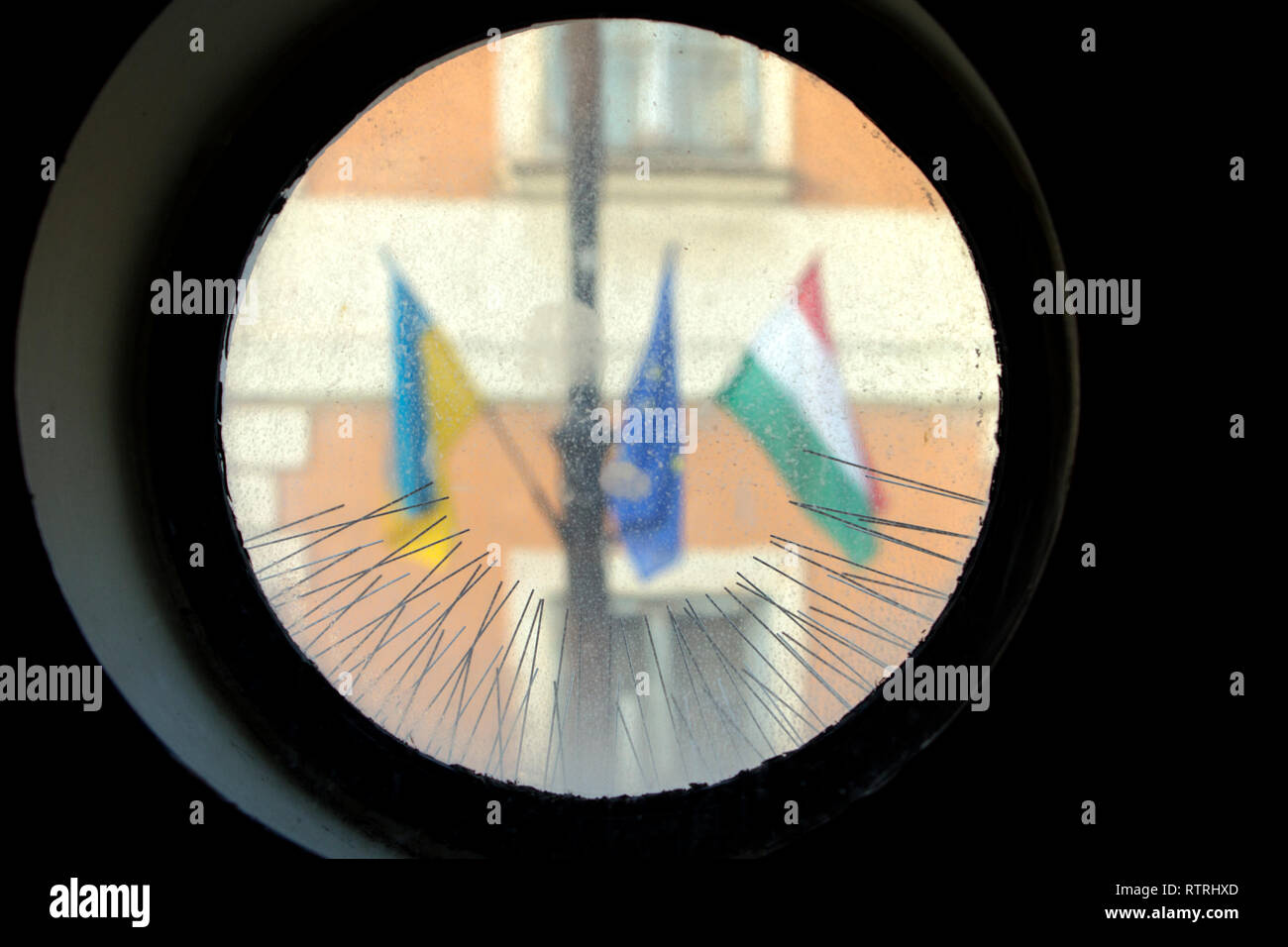 Hungarian and European Union flags surrounded by thorns as seen from a church window's round blurred glass. - Stock Image