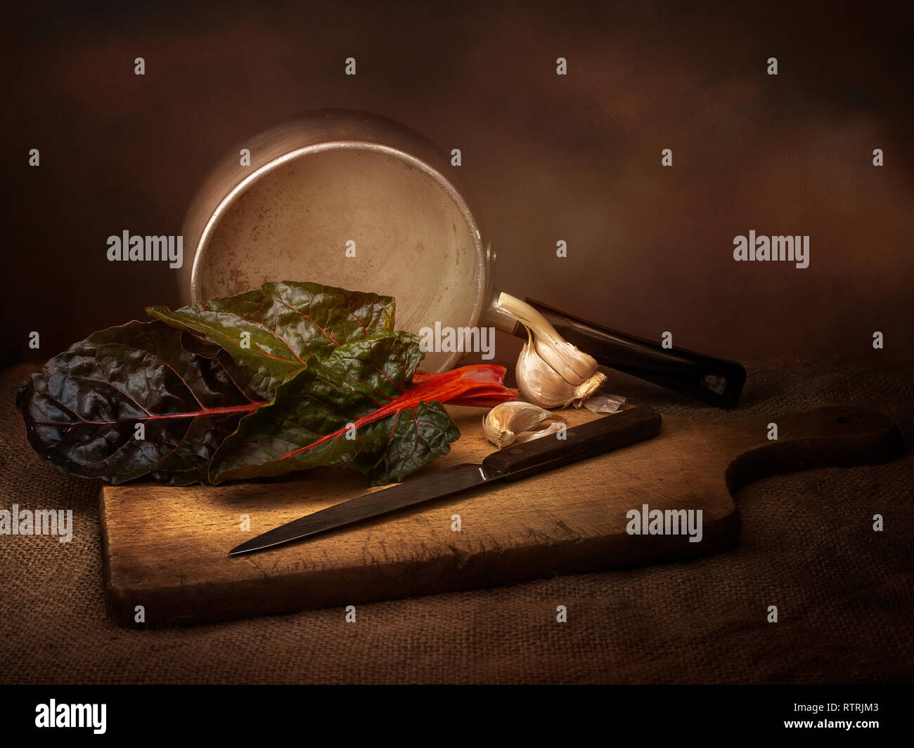 Ruby aka Swiss chard vegetable food preparation, still life with garlic. Chiaroscuro style light painting. Beta vulgaris. - Stock Image