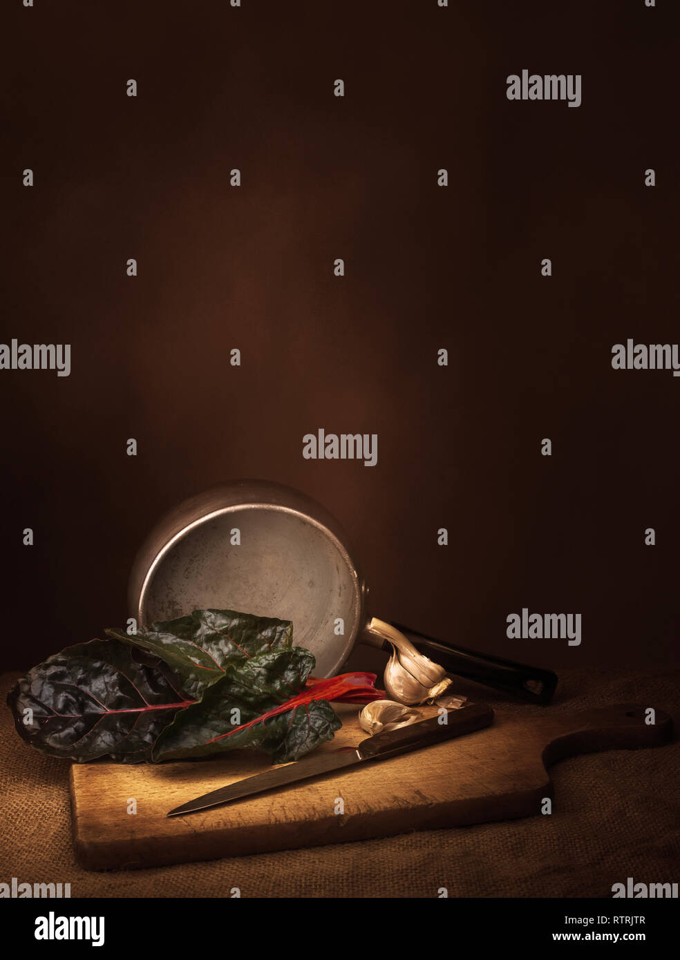 Ruby aka Swiss chard vegetable food preparation, still life with garlic. Chiaroscuro style light painting. Beta vulgaris. Vertical composition. - Stock Image