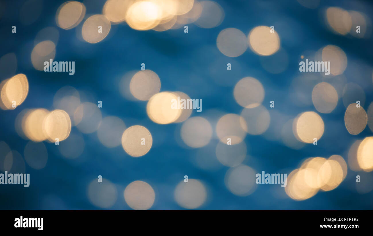 Glistening and shimmering blue blurred ocean surface at sunset or sunrise with sun reflections on it - Stock Image