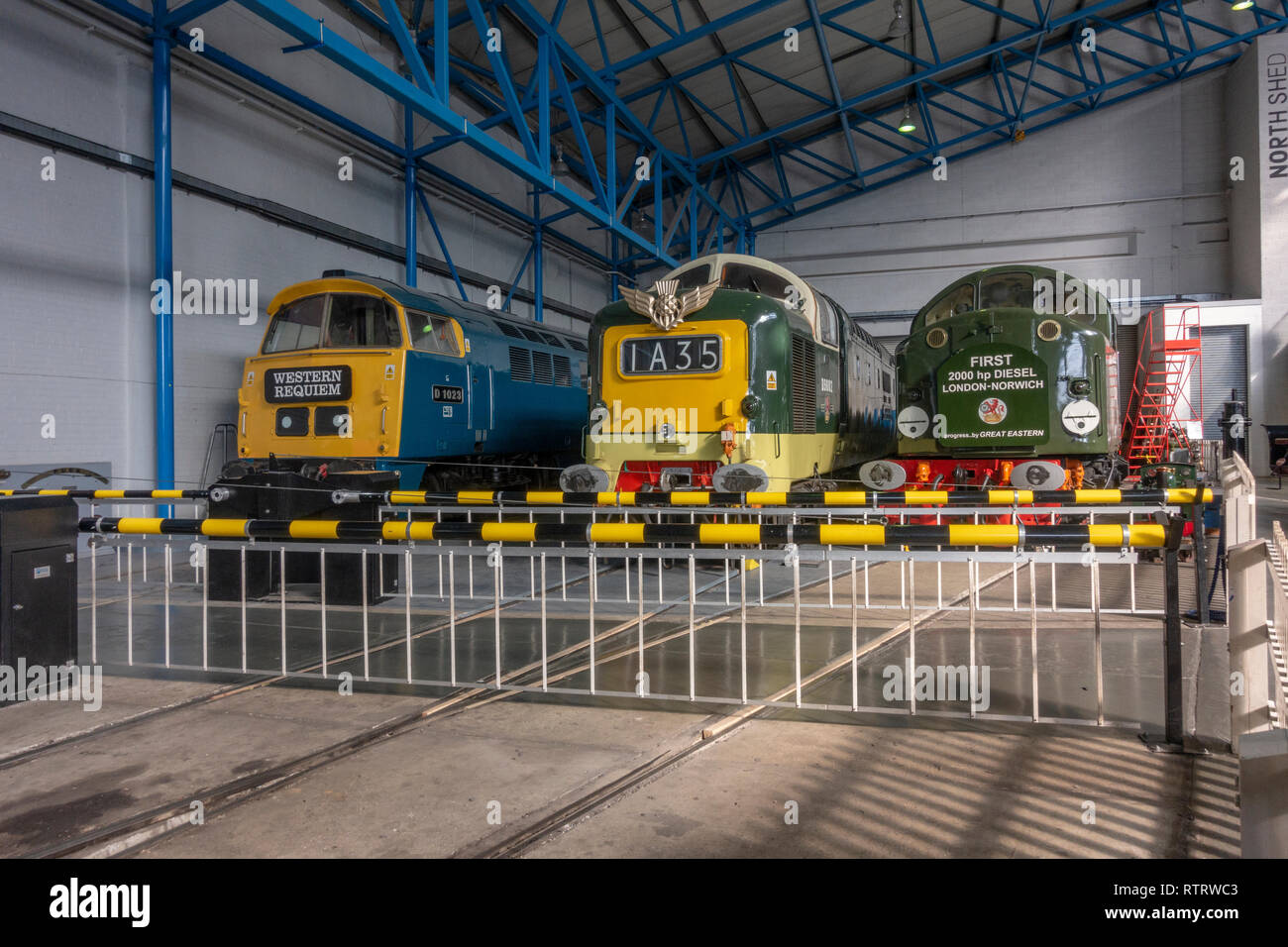 Three diesel locomotives behind a level crossing display in the National Railway Museum, York, UK. Stock Photo