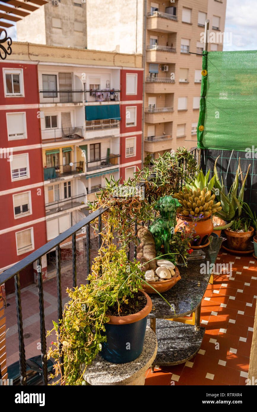 A view to street from a balcony full of flowers. - Stock Image