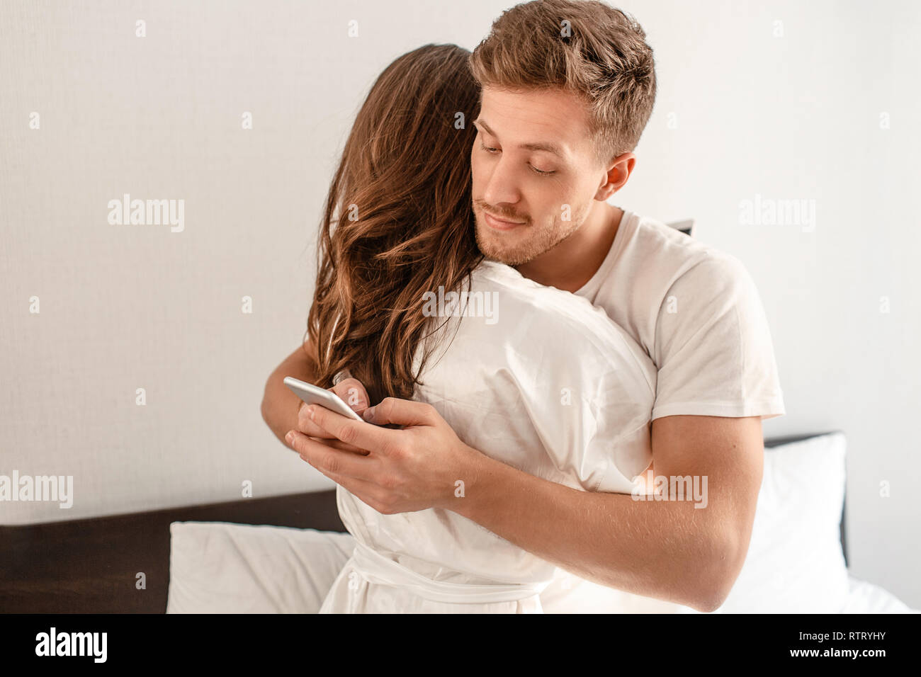 Young couple in the bedroom after waking up. Smiling unfaithful man is cheating and texting lover on the phone while hugging his girlfriend - Stock Image