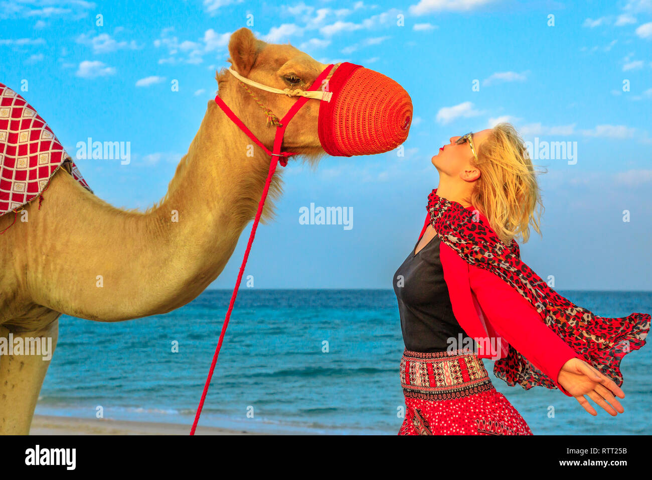 Carefree blonde woman encounter with camel on a beach of Khor al Udaid in Persian Gulf of southern Qatar. Caucasian tourist after camel ride, a - Stock Image