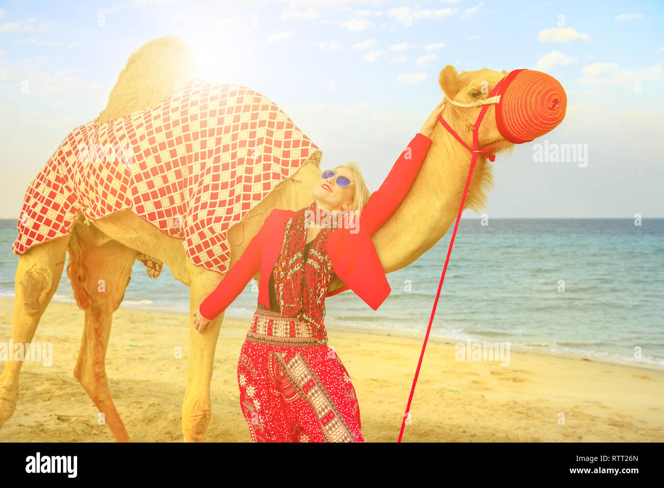Happy blonde woman with camel on a sand beach of Khor al Udaid in Persian Gulf of southern Qatar at sunset sky. Caucasian tourist after camel ride, a - Stock Image