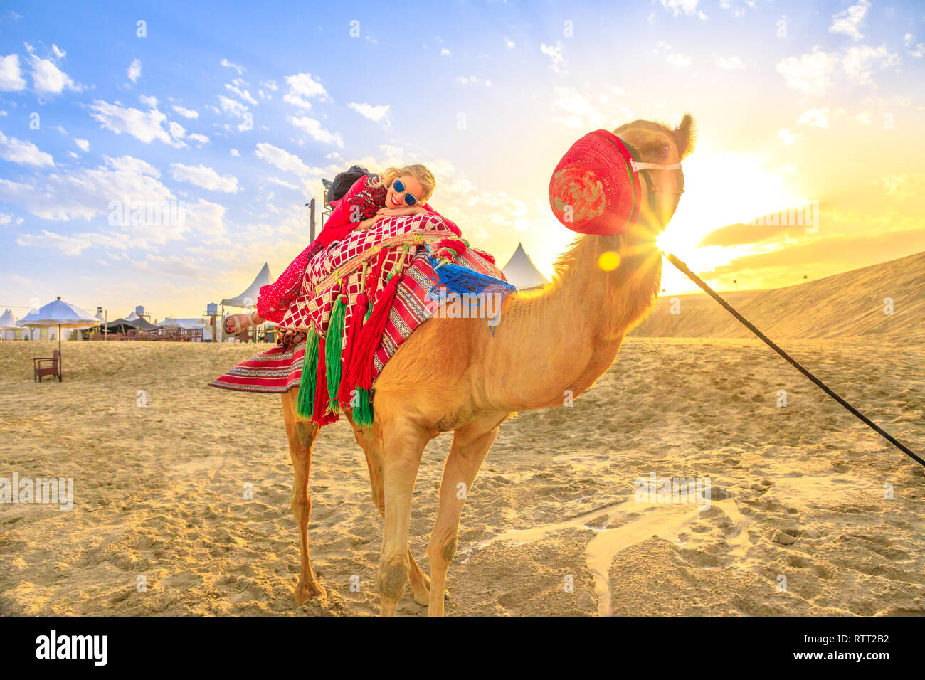 Happy woman lying over a camel on sand dunes of beach at Khor al Udaid in Persian Gulf, southern Qatar. Caucasian tourist enjoys camel ride at sunset - Stock Image