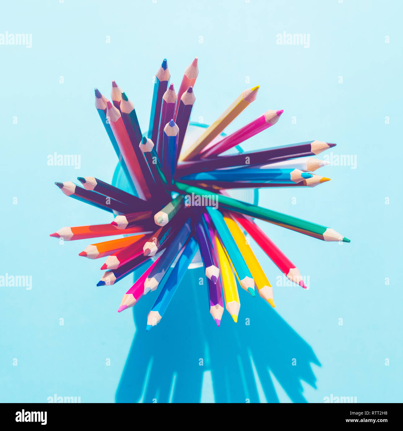 Top view of colorful pencil in glass with long shadow on pastel background.business creativity concept ideas - Stock Image