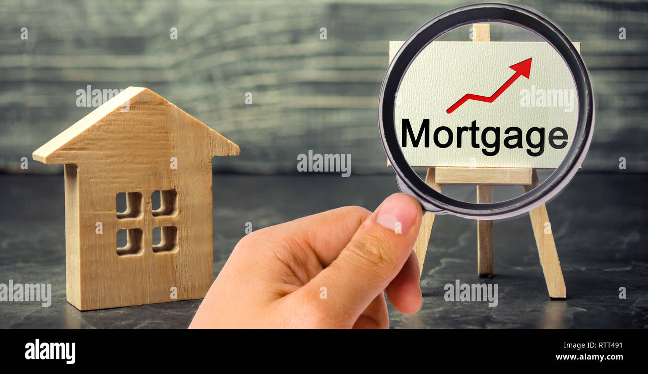 Wooden house and the inscription Mortgage and up arrow. Raising mortgage rates and tax. The increase in interest charges. Reduced demand for housing.  - Stock Image
