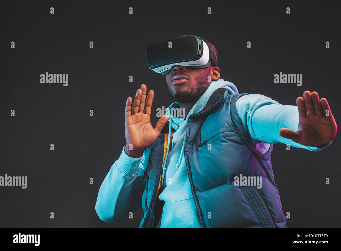 Gaming concept. African casual man in warm seasonal outdoor clothes wearing mobile VR headset enjoying new reality in dark room. Fashion and Innovatio Stock Photo