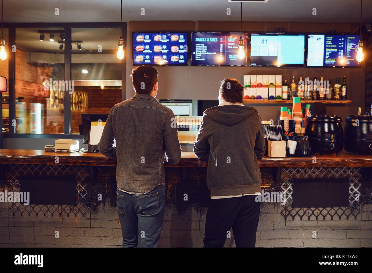 Two men choose food in a fast food restaurant. - Stock Image
