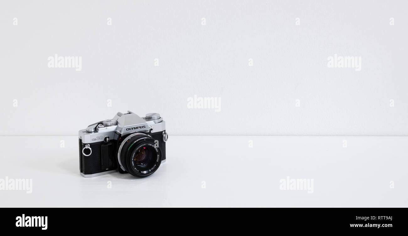Prague, CZECH REPUBLIC - FEBRUARY 28, 2019: Olympus OM-30 a 35mm film SLR camera by Olympus Corporation, laid on white desk in front of white wall - Stock Image