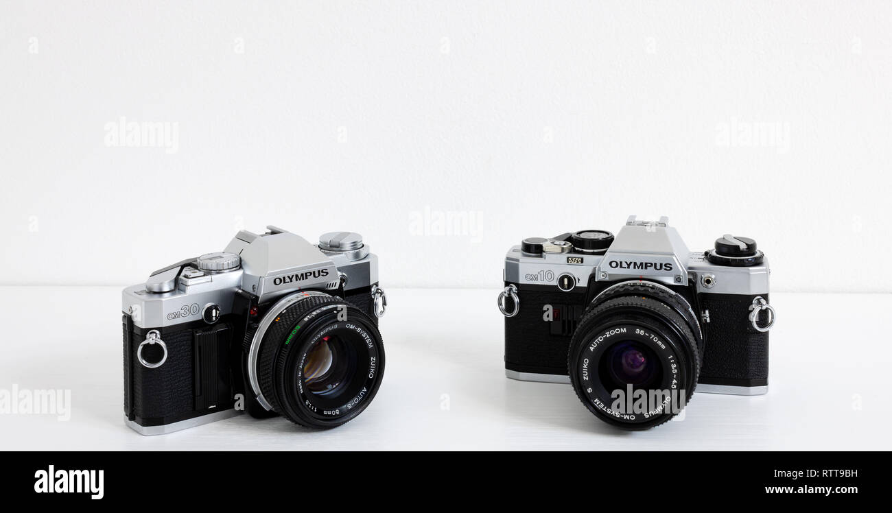 Prague, CZECH REPUBLIC - FEBRUARY 28, 2019: Olympus OM-10 and OM-30 a 35mm film SLR cameras by Olympus Corporation, laid on white desk in front of whi - Stock Image