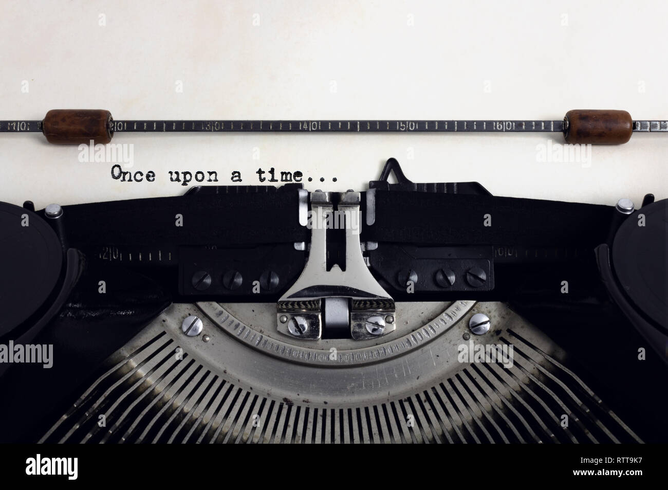 Old retro vintage black typewriter with close-up typing text Once upon a time as heading on aged paper Stock Photo