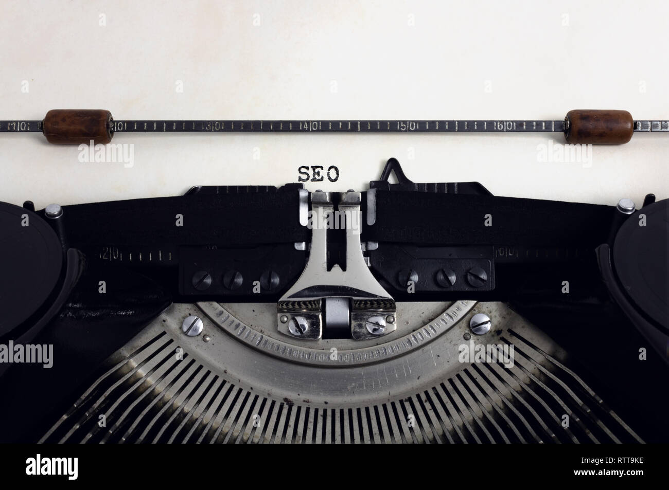 Old retro vintage black typewriter with close-up typing text SEO as heading on aged paper Stock Photo