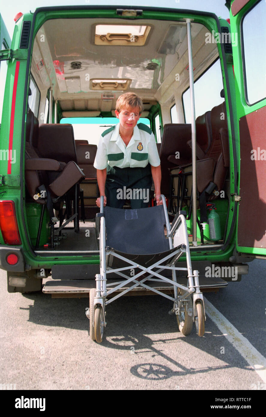 Ambulance crew showing how to lift a wheelchair onto an ambulance - Stock Image