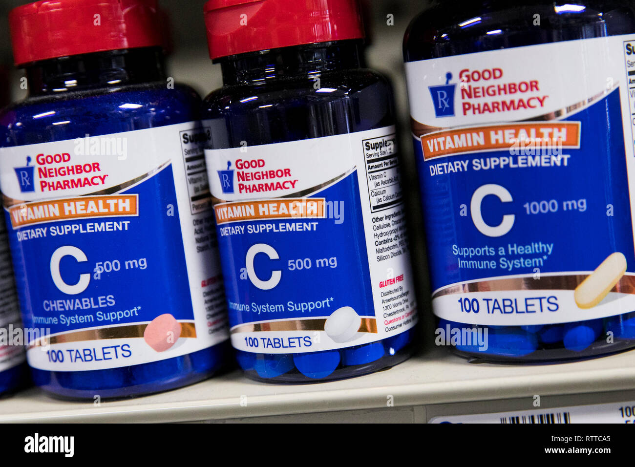 Bottles of Vitamin C supplements photographed in a pharmacy. - Stock Image