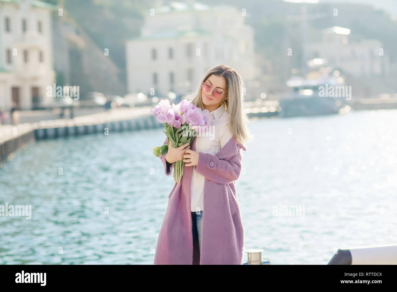 Beautiful happy woman with straight hair holding a bouquet of pink tulips one spring sunny day. - Stock Image