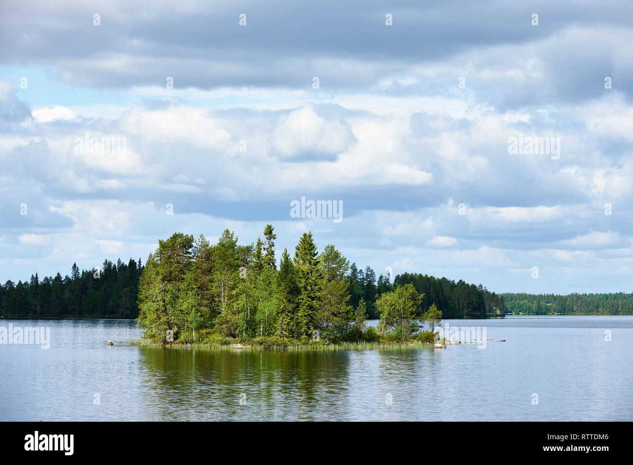 Relaxing Finnish landscape,  with lake, forest, trees, sky and reflected clouds - Stock Image
