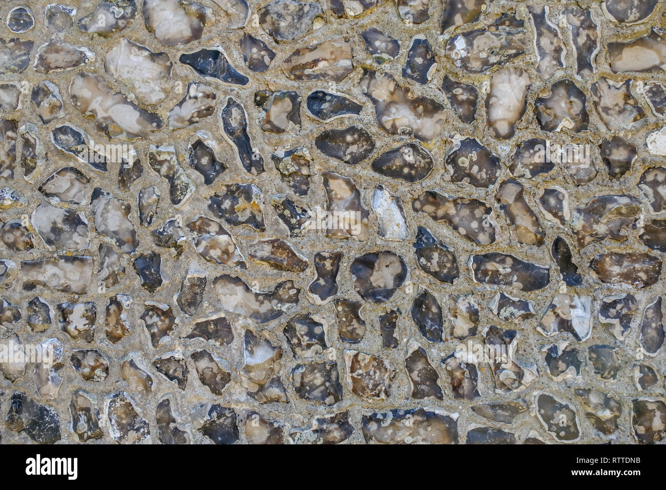 Closeup of flint wall, typical style found in Sussex. Large stones with mortar which makes an interesting background or graphic resource. - Stock Image