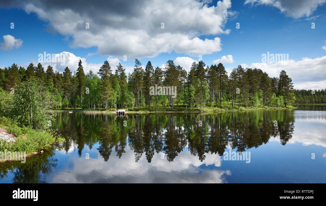Relaxing Finnish landscape,  with lake, a little pier, forest, trees, sky and reflected clouds - Stock Image