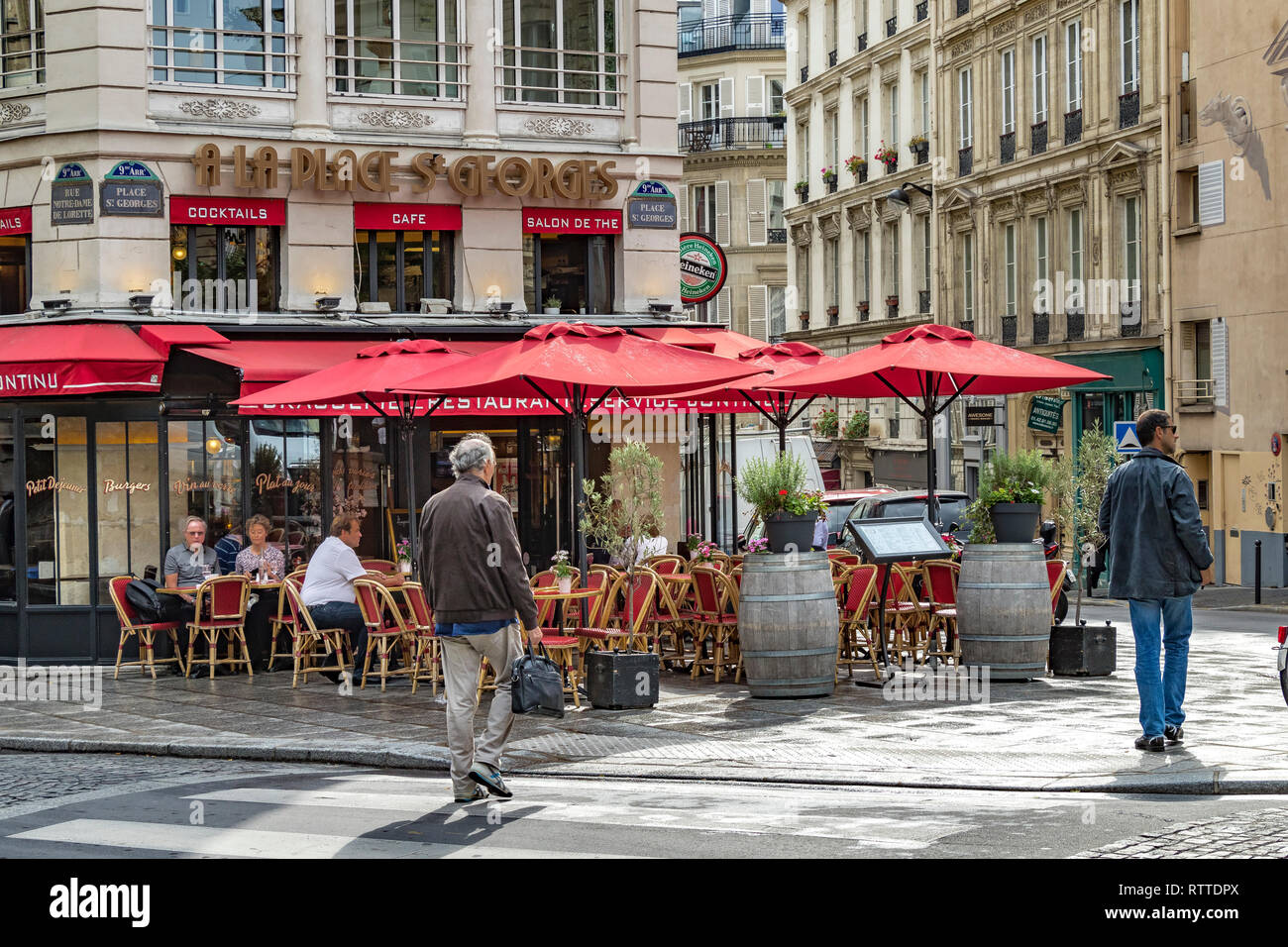 People sitting outside À la Place Saint-Georges,a cafe restaurant in The St Georges area of  the9th arrondissement of of Paris in the late afternoon . - Stock Image