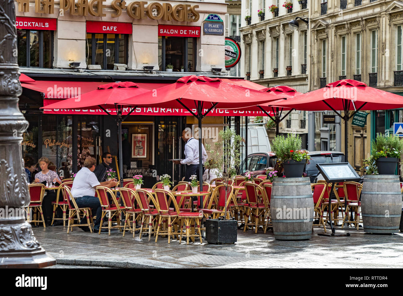 People sitting outside À la Place Saint-Georges,a cafe restaurant in The St Georges area of  the9th arrondissement of of Paris in the late afternoon . Stock Photo
